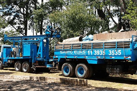 Caminhão azul carregado com equipamentos.