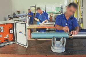 Homens fazendo a manutenção em cilindros metálicos.