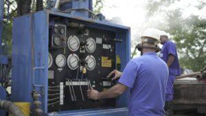 Homem operando máquina de perfuração.