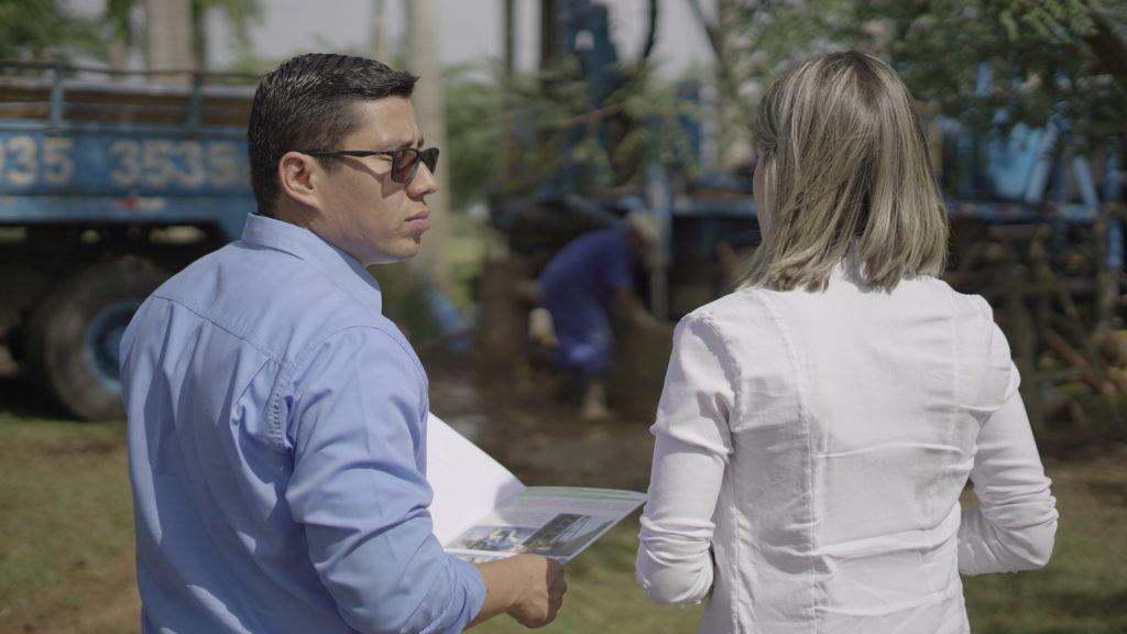 Um homem e uma mulher conversando sobre a perfuração de um poço artesiano.
