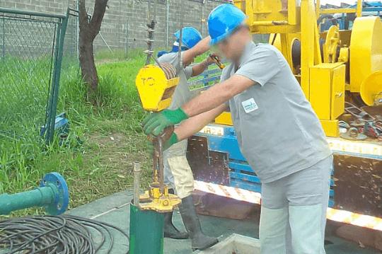Dois homens trabalhando na manutenção de um poço artesiano.